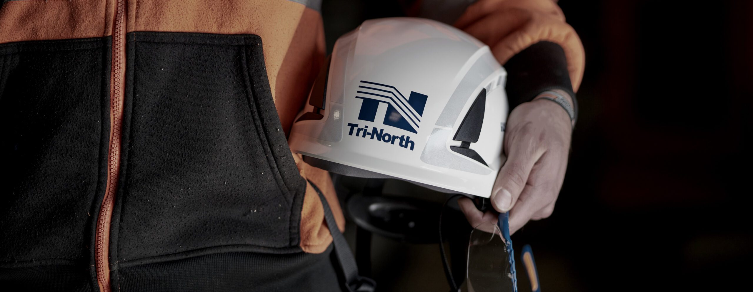 Close up view of a construction crew member holding a Tri-North hard hat