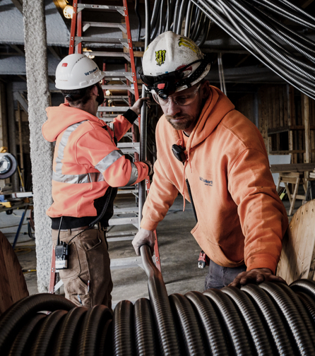 Members of the Tri-North construction team work together to run cable at a project site.