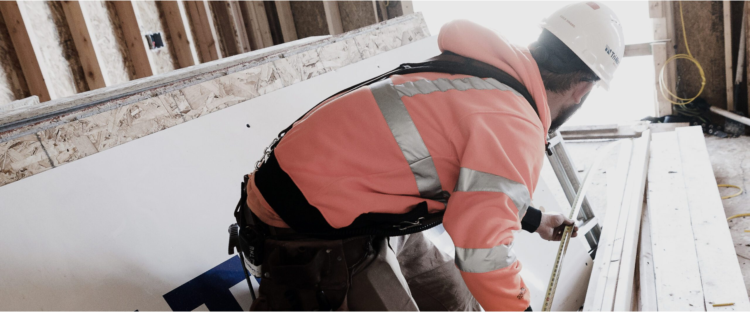A member of Tri-North's construction crew measures lumber on a job site.