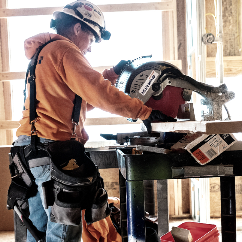 A member of Tri-North's construction crew cuts lumber using a circular saw.