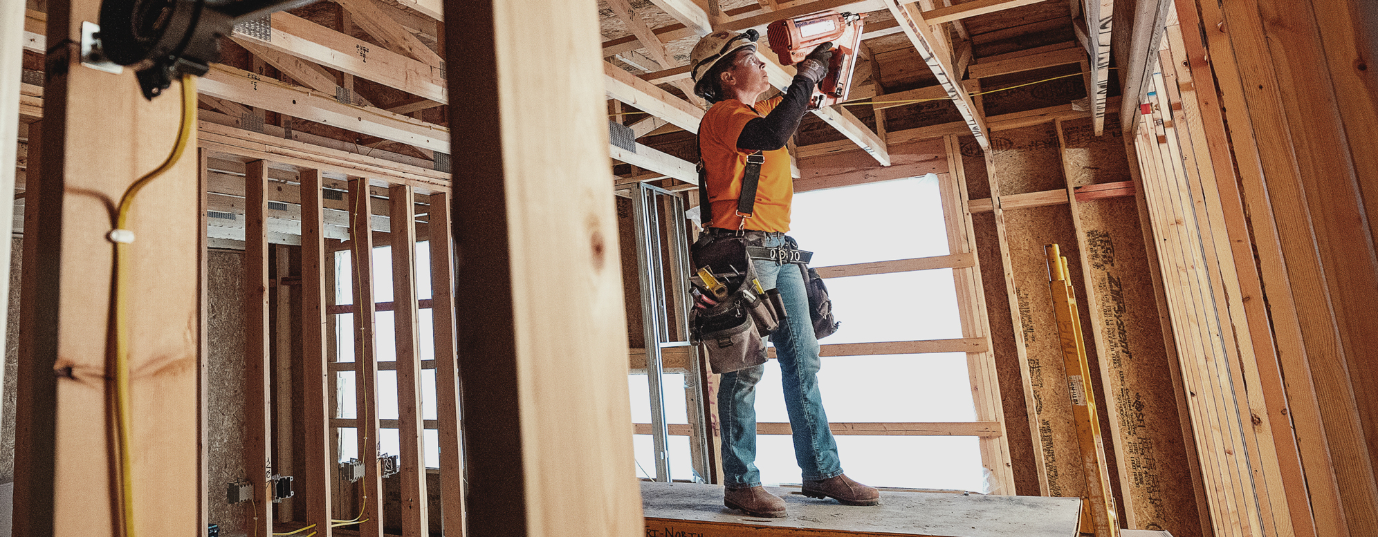 A commercial construction worker uses a nail gun at a Tri-North build site.