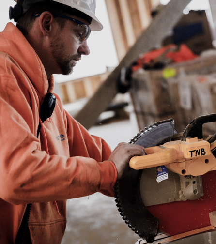 A worker in a Tri-North sweatshirt uses a circular saw at a construction site.