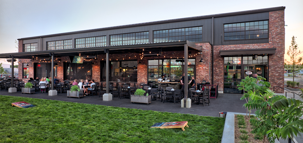 Back patio and outdoor seating with games for ABV Social restaurant in Wisconsin as built by Tri-North Builders.