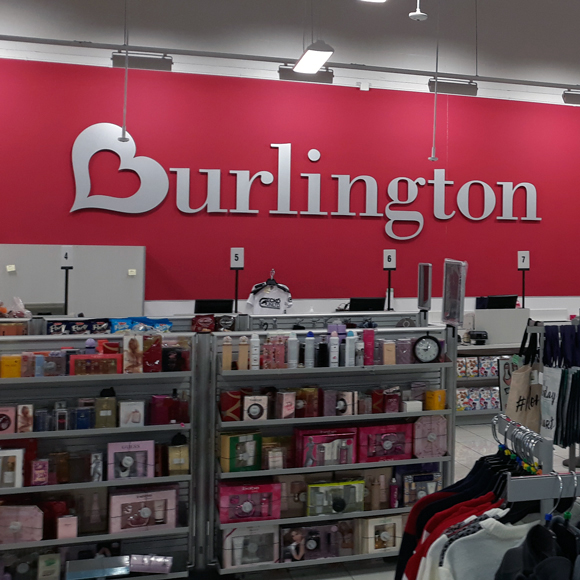 A sign with the Burlington logo is featured on a wall behind shelves of product.