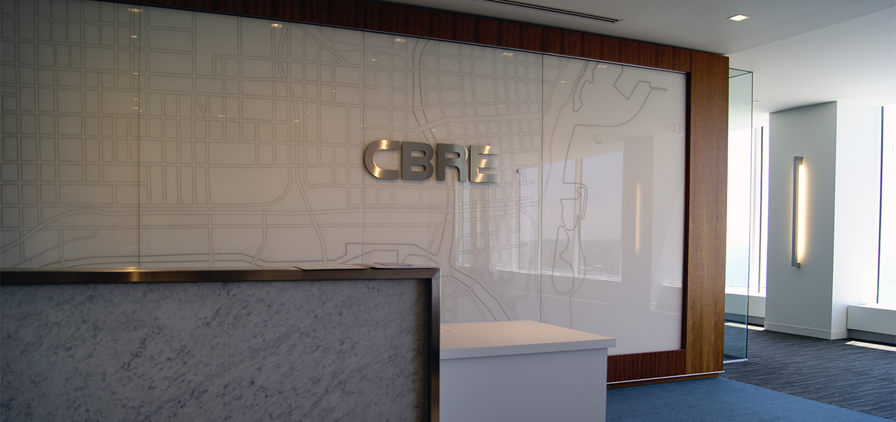 CBRE building reception area with logo and map behind desk as built by Tri-North Builders in Wisconsin.