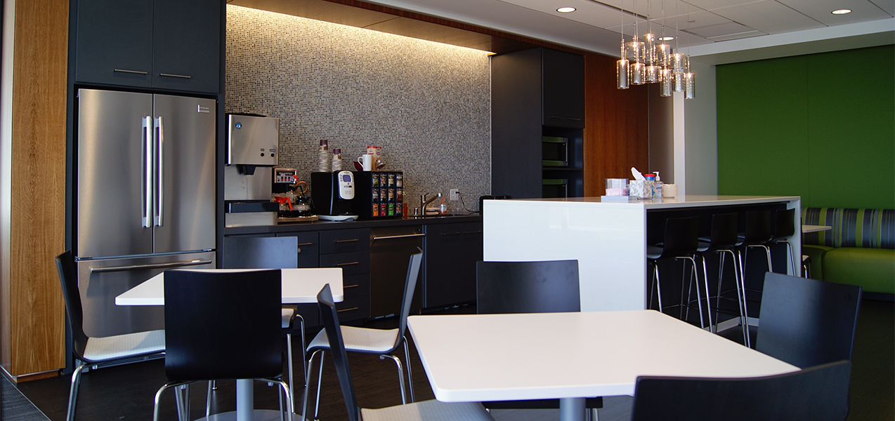Break room area featuring coffee maker, counter, fridge and tables inside the Tri-North Builders CBRE construction project.