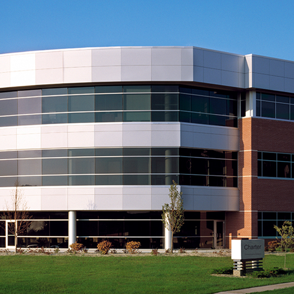 Front of building and windows with lawn from the Tri-North Builders Charter Communications Building in Wisconsin.