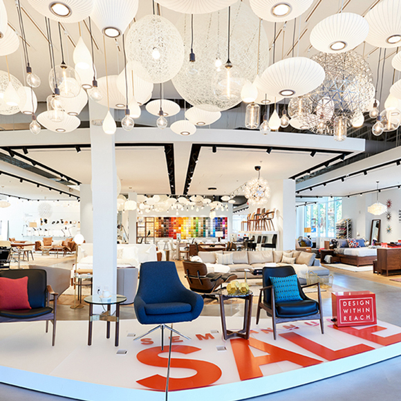 White light fixtures hang at the entrance of a Design Within Reach store built by Tri-North.
