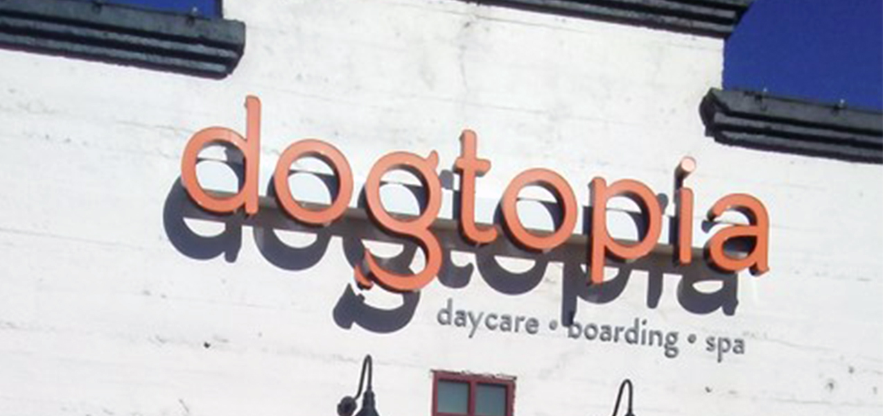 The Dogtopia sign is seen against the white brick facade of one groomer location.
