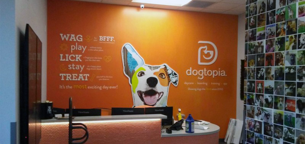 A bright orange wall greets pet owners at the entrance to a Dogtopia built by Tri-North.