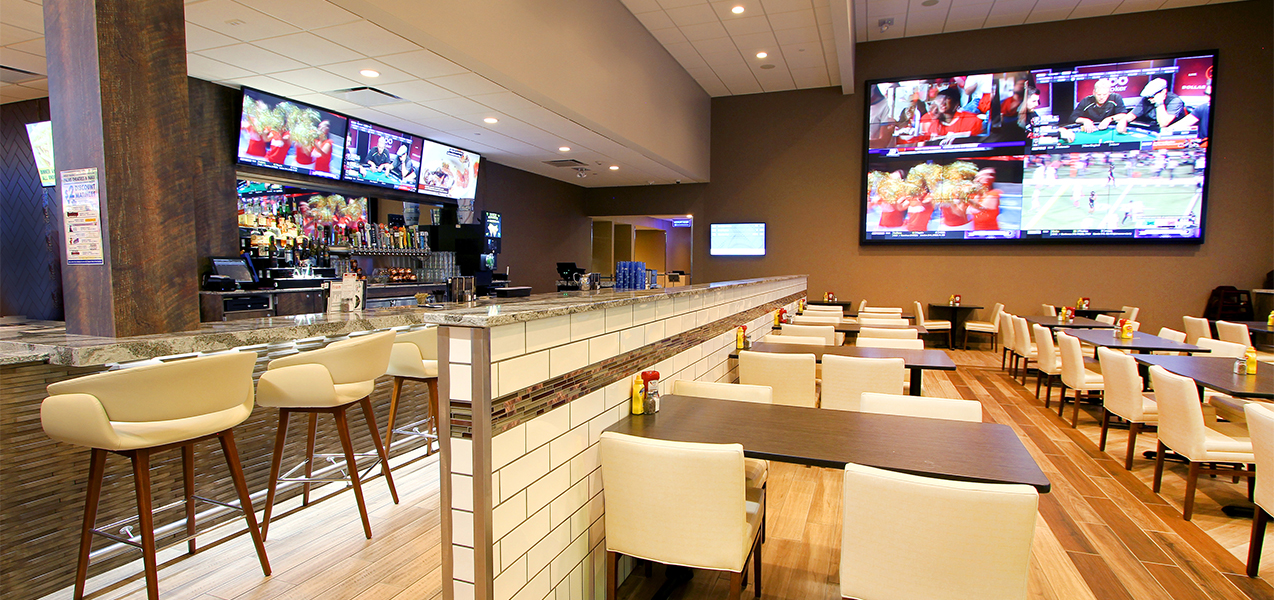Bar with bar stools, tables, booths inside the Fridley Palms movie theater in Waukee, IA, remodeled by Tri-North Builders.