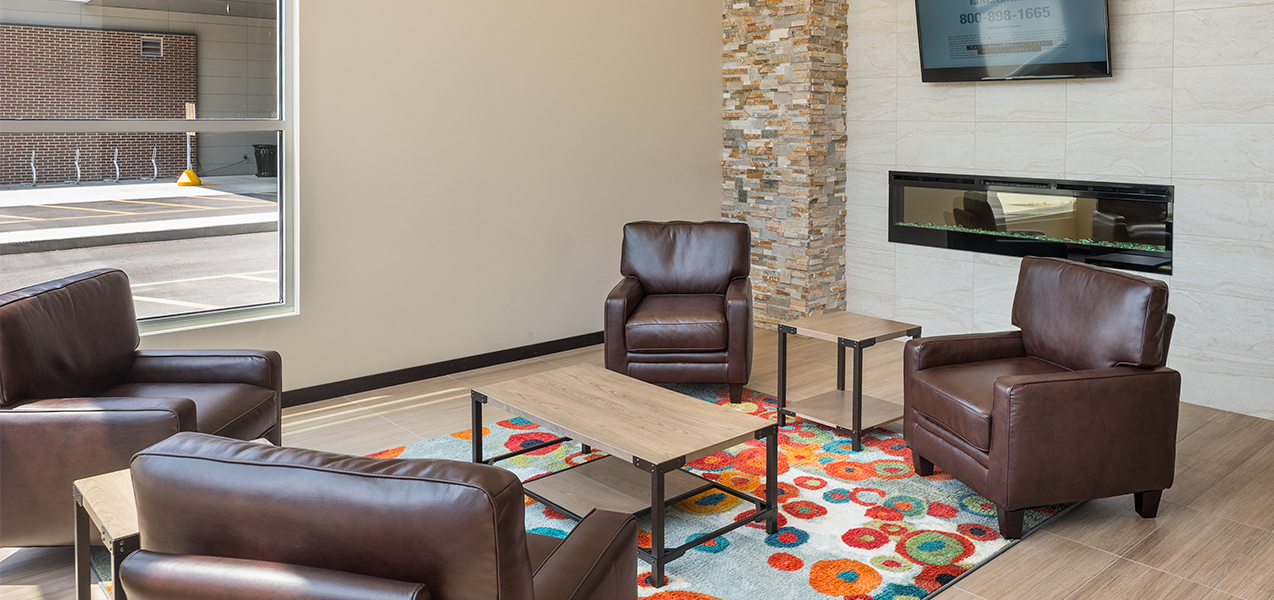 Sitting area with chairs and glass table inside the Galaxie condominium building in Madison, WI.