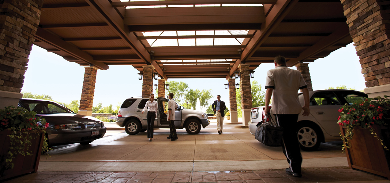 Drop off area at front entrance of the Grand Geneva Resort in Wisconsin showing cars and valets.