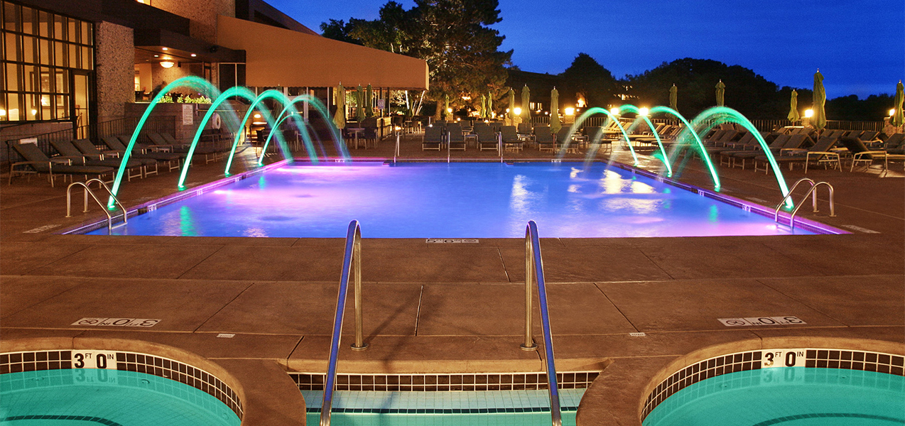 Lighted pool and fountains at night at the Geneva Resort in Lake Geneva, WI, which is a Tri-North Builders project.