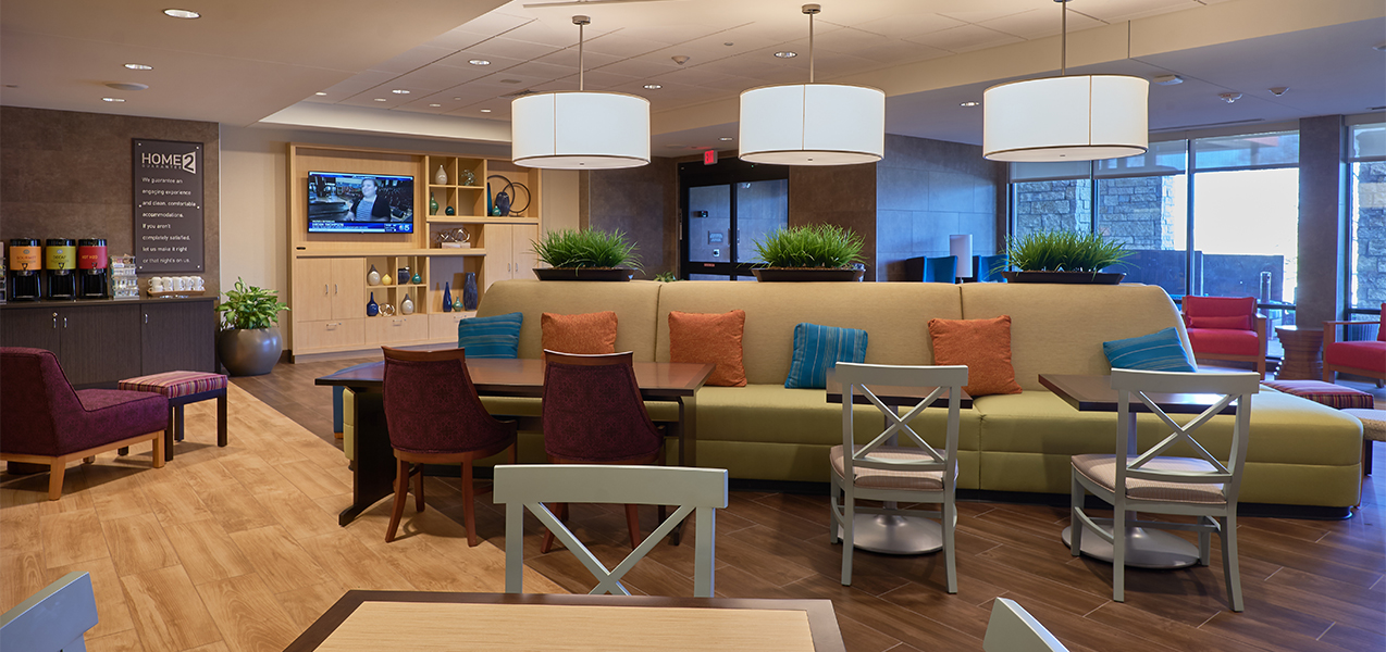 Sitting and lounge area with tables and chairs inside the Home2Suites by Hilton Madison in Wisconsin.
