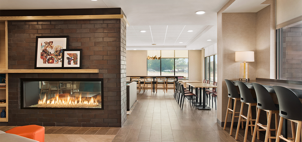 Tables, chairs & fireplace inside Tri-North Builders project at Home2Suites by Hilton Madison Central Alliant Energy Center.