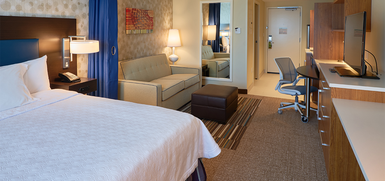 Tri-North Builders remodeled room with bed inside the Home2Suites by Hilton Madison Central Alliant Energy Center.