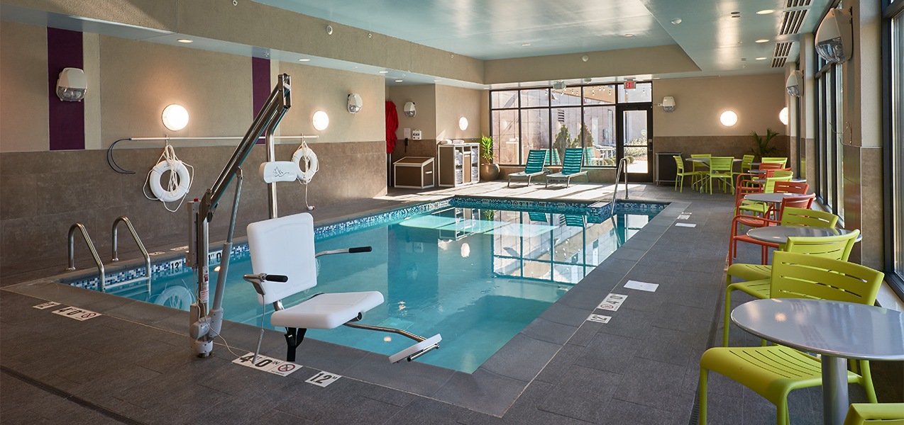 Handicapped accessible pool and chairs at the Home2Suites by Hilton Madison Central Alliant Energy Center project.
