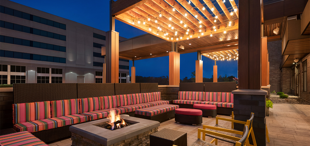 Outdoor seating area and fire pit from the Tri-North Builders Home2Suites by Hilton Madison Central Alliant Energy Center project.