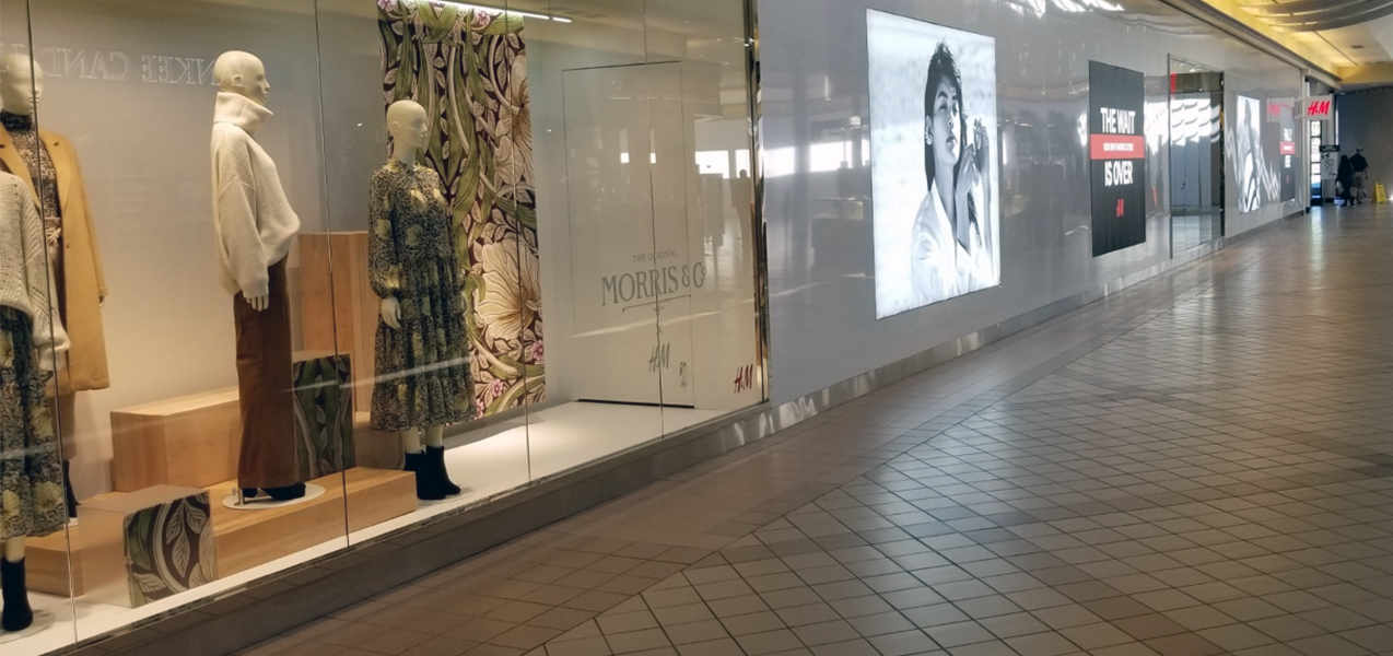 Signage in the windows of an H&M store, located in a shopping mall.