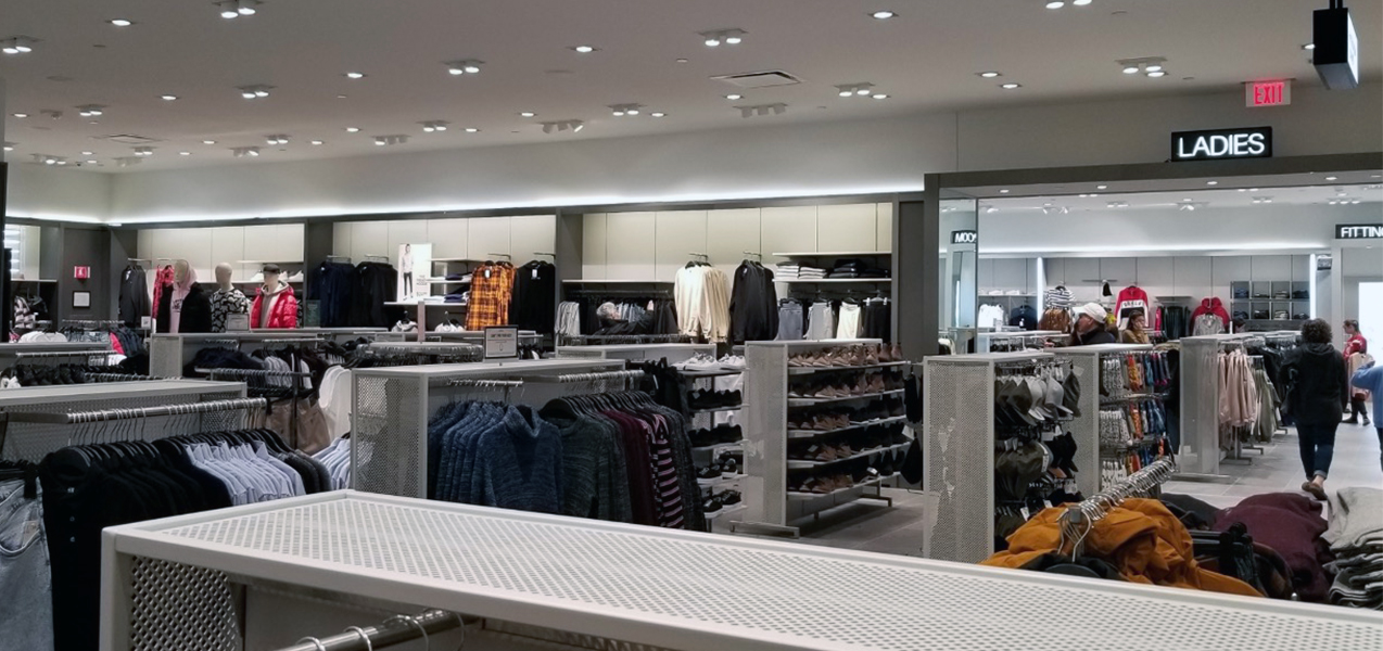 Wall and free-standing racks of clothing are seen in front of a sign directing shoppers to the Ladies Fitting Room.