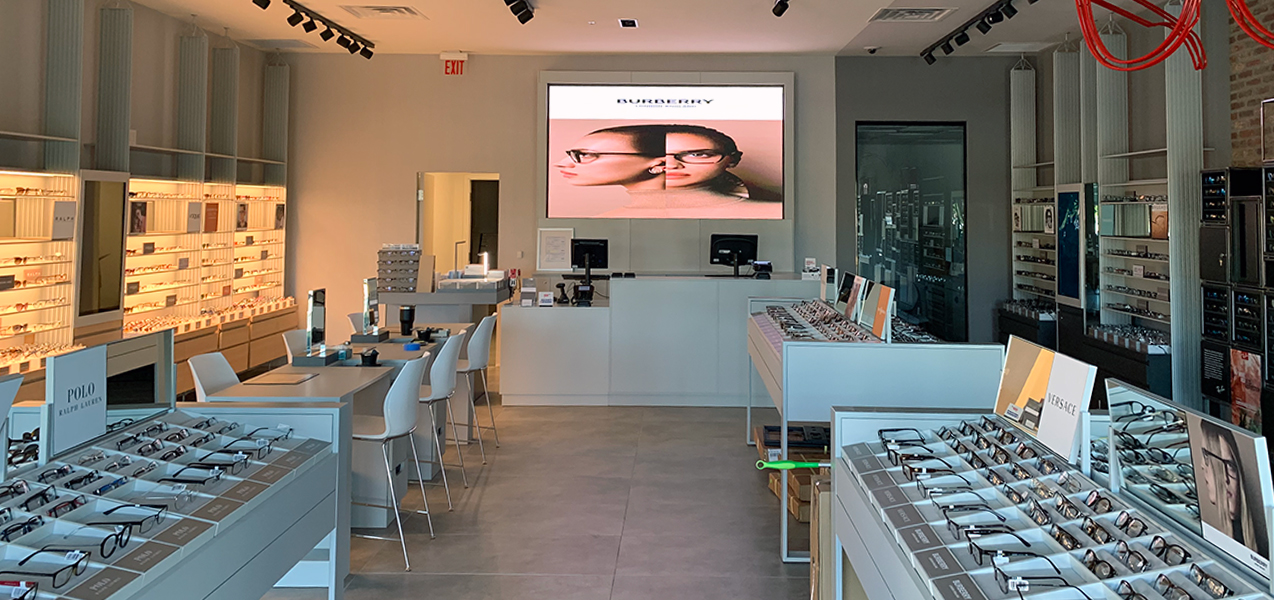 Free-standing cases and backlit wall units display glasses at a LensCrafters location built by Tri-North.