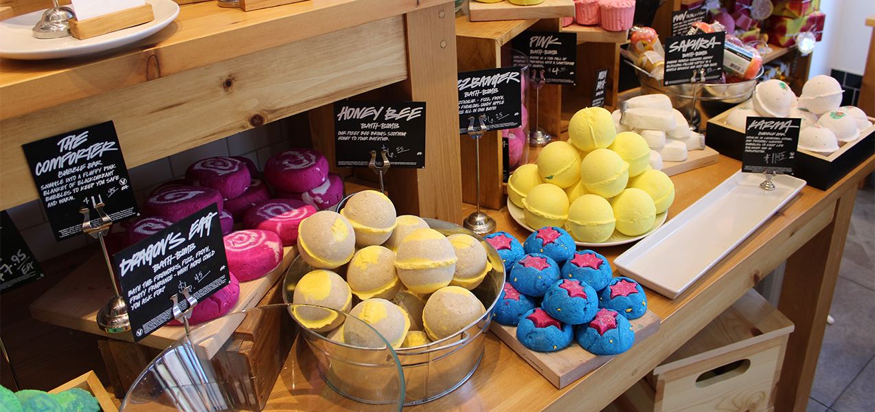 Bath bombs fill a wooden table at a Lush retail store, a Tri-North project.