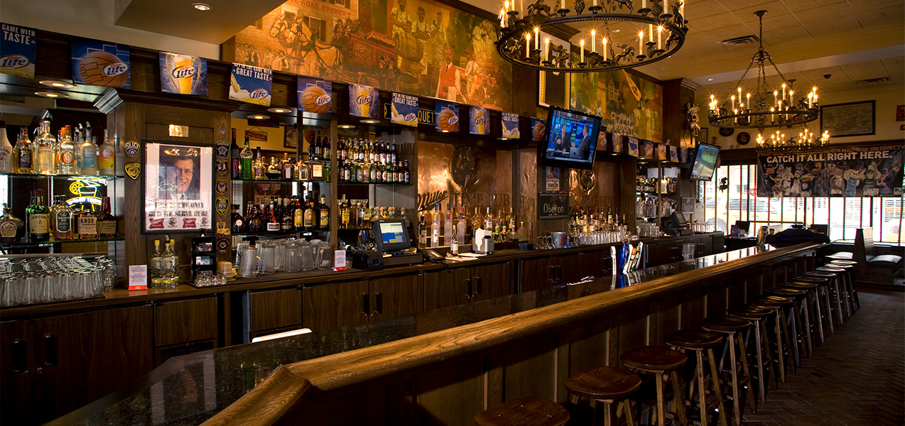 Long shot of the bar with barstools inside the Miller Time Pub