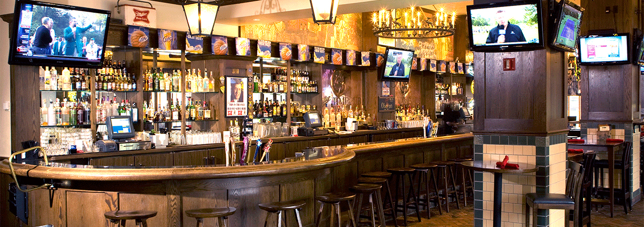 Long wooden bar, tables, chairs and television as built by Tri-North Builders inside the Miller Time Pub.
