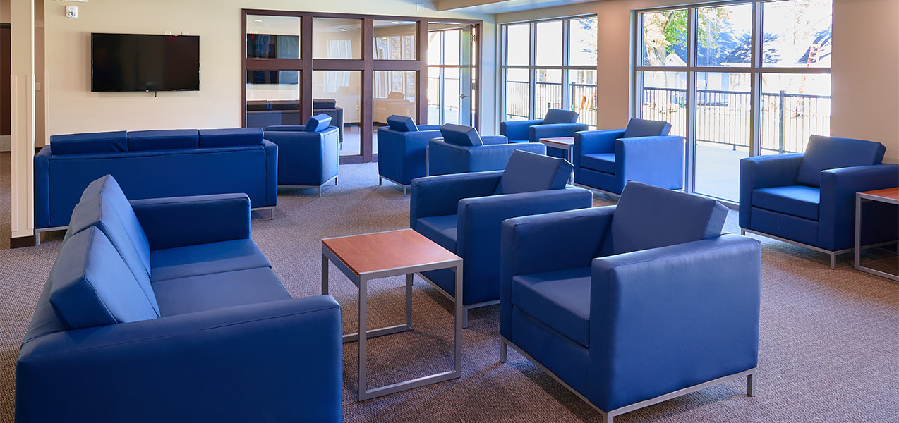 Common room with blue chairs, tables and window inside the Newman Heights apartment building built by Tri-North Builders.