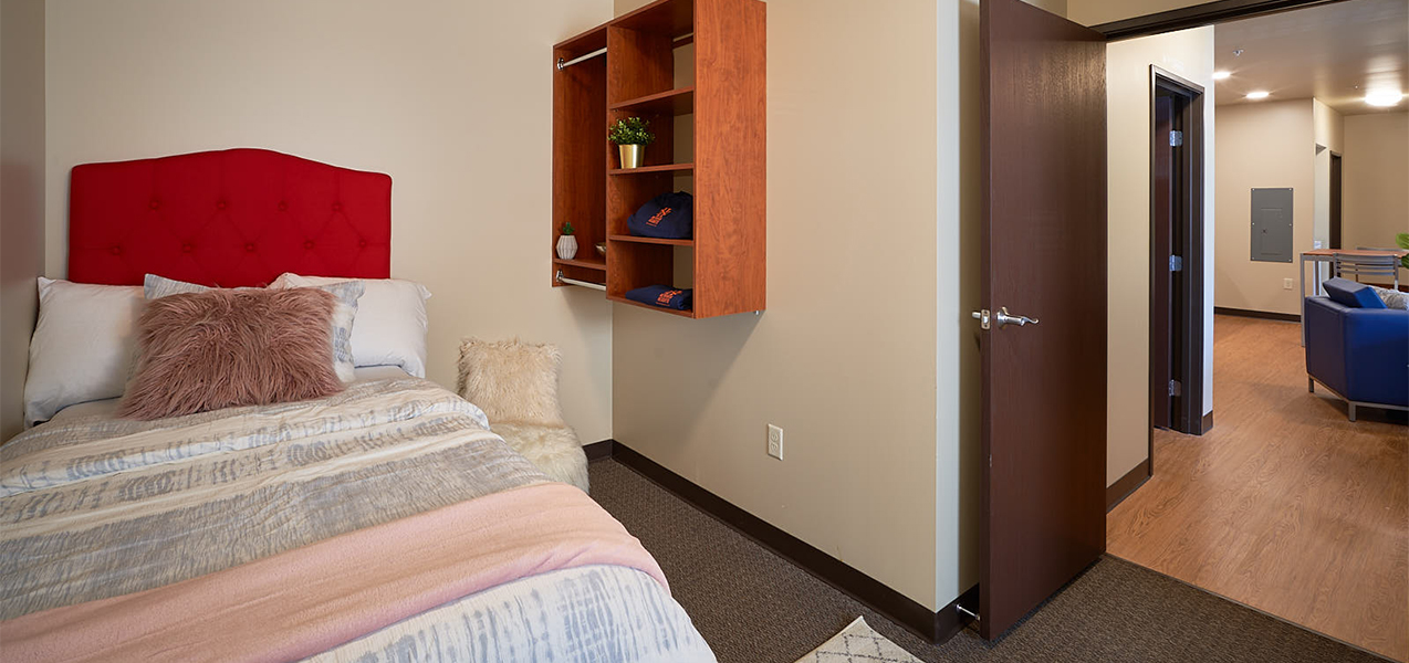 Bedroom and bed showing living room area inside the Newman Heights student housing building in Platteville, WI