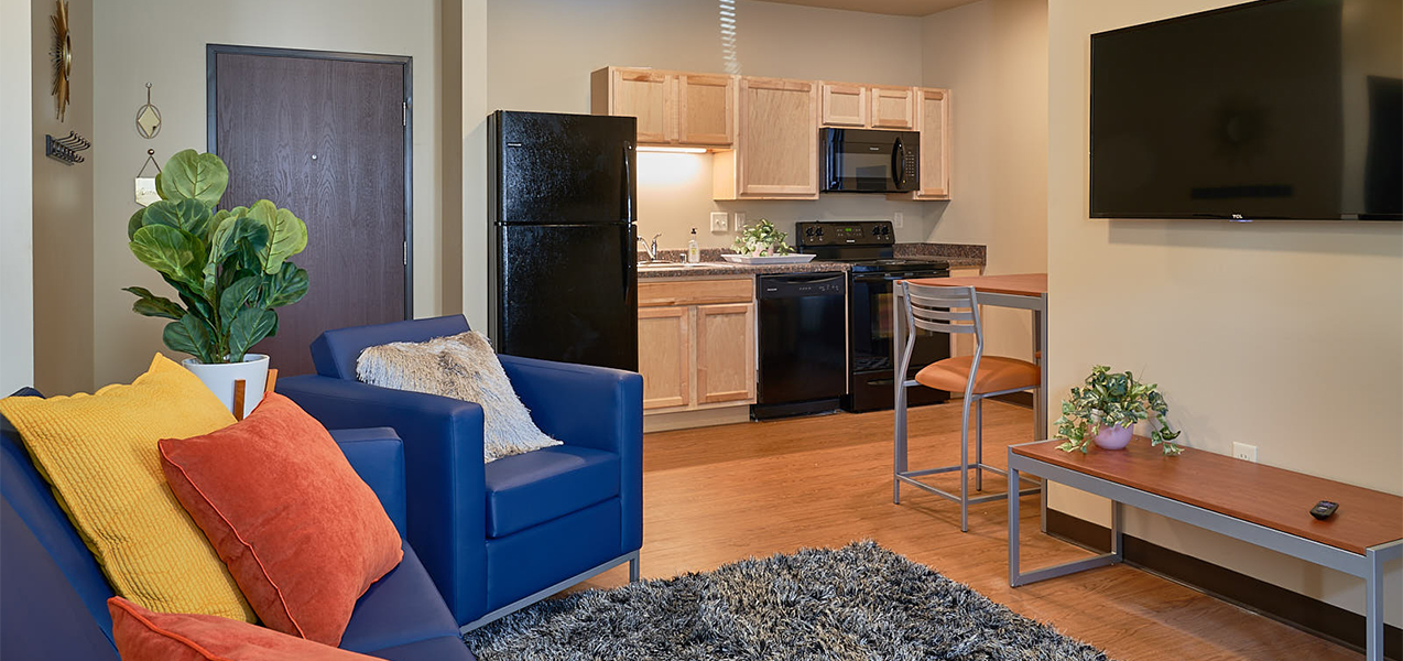 Living room area showing kitchen inside Tri-North Builders remodeled student housing apartments at Newman Heights.