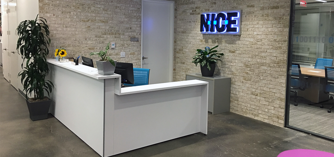 The entrance of the NICE office in Richardson, Texas features exposed brick. This was a Tri-North Builders project. We can help you with your project, too.