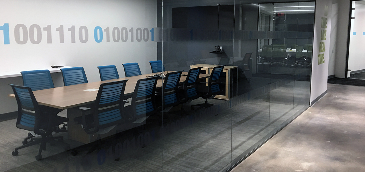 A glass wall offers a view of a conference table and chairs at the NICE office built by Tri-North.