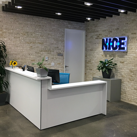 The reception desk and glowing sign welcome visitors to NICE, a Tri-North building.