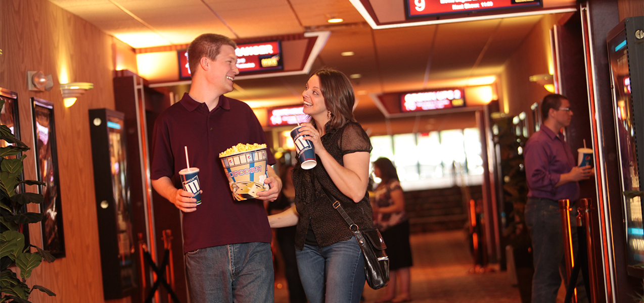 Two movie goers with popcorn and soda walking to movie theaters inside the Marcus Point Cinema in Madison.