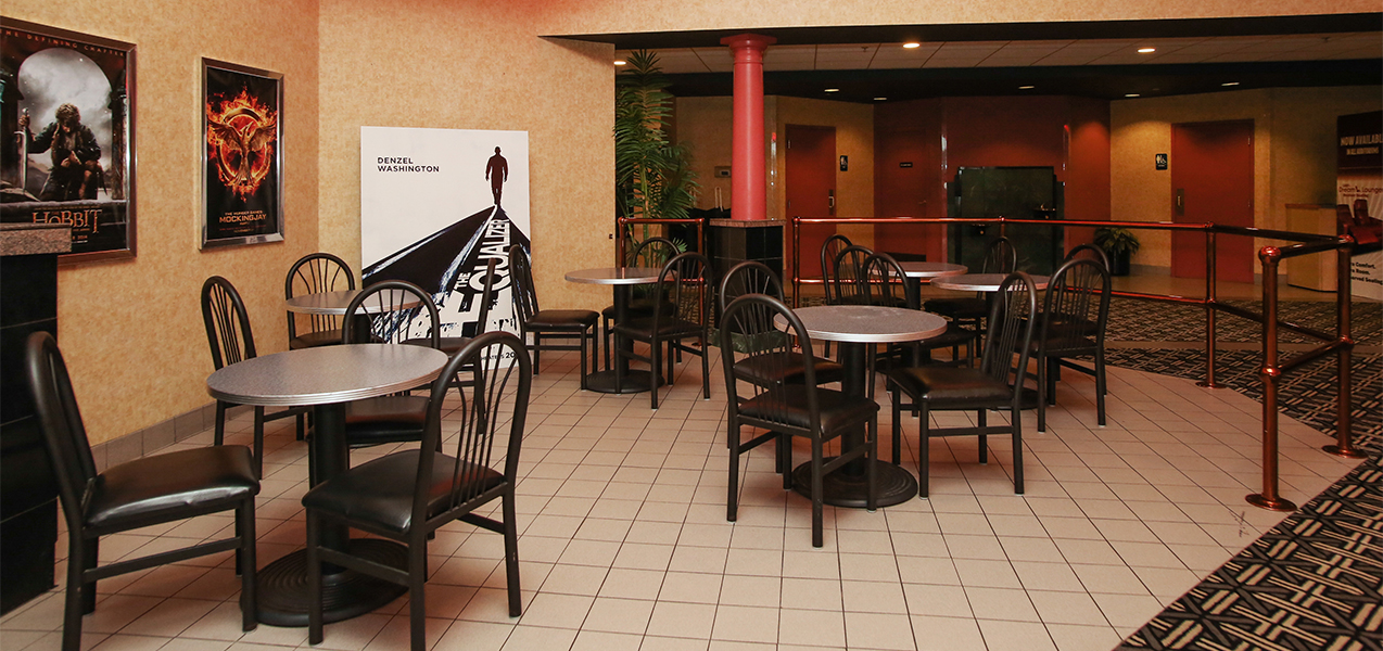 Sitting area with tables and chairs inside the Rosemont movie theater from a Tri-North Builders construction project.