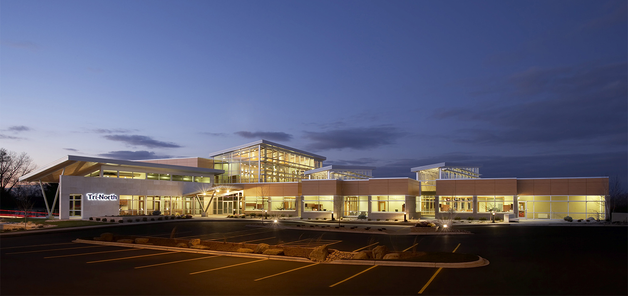The entire Tri-North Builders headquarters at night with the office lights on located in Wisconsin.