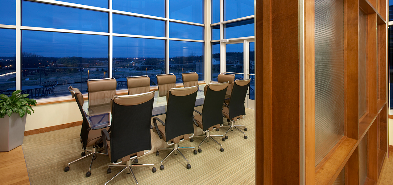 Conference room with table and chairs in front of windows inside the Tri-North Builders headquarters.