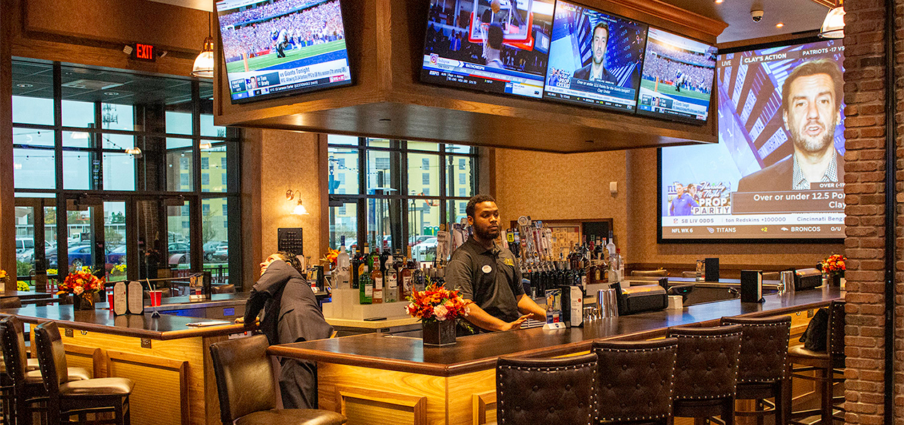 Full bar, bartenders, barstools and television screen in lounge area of the Movie Tavern Brookfield.