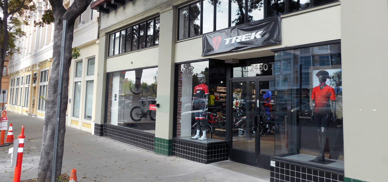 Mannequins and bikes are seen in the entrance windows of a Trek bike store built by Tri-North.