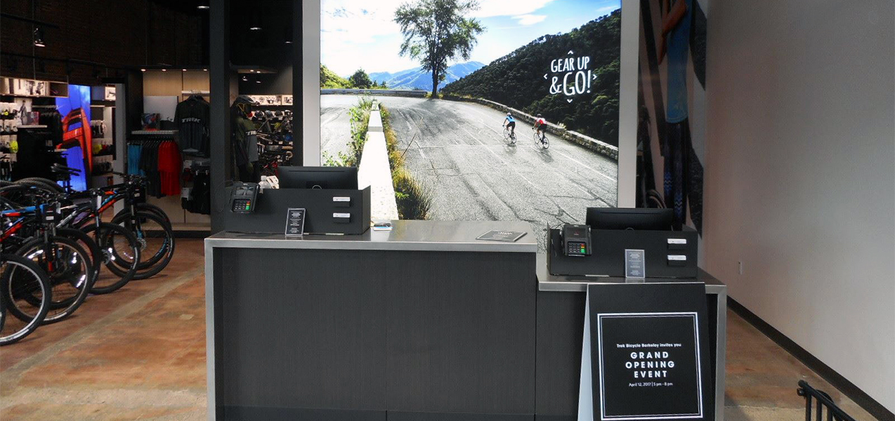A lit screen wall stands behind the cash register at the Trek store, a Tri-North project.