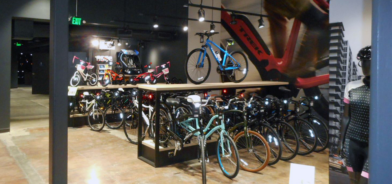 Bikes are displayed in metal and wood racks at Trek Bikes, a project by Tri-North Builders.