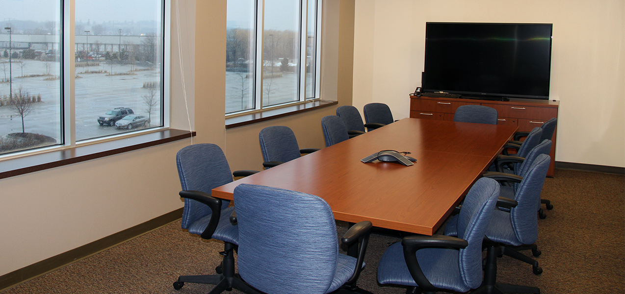 Conference room, table and chairs with window overlooking parking lot at the Tri-North Builders UW Health Offices.