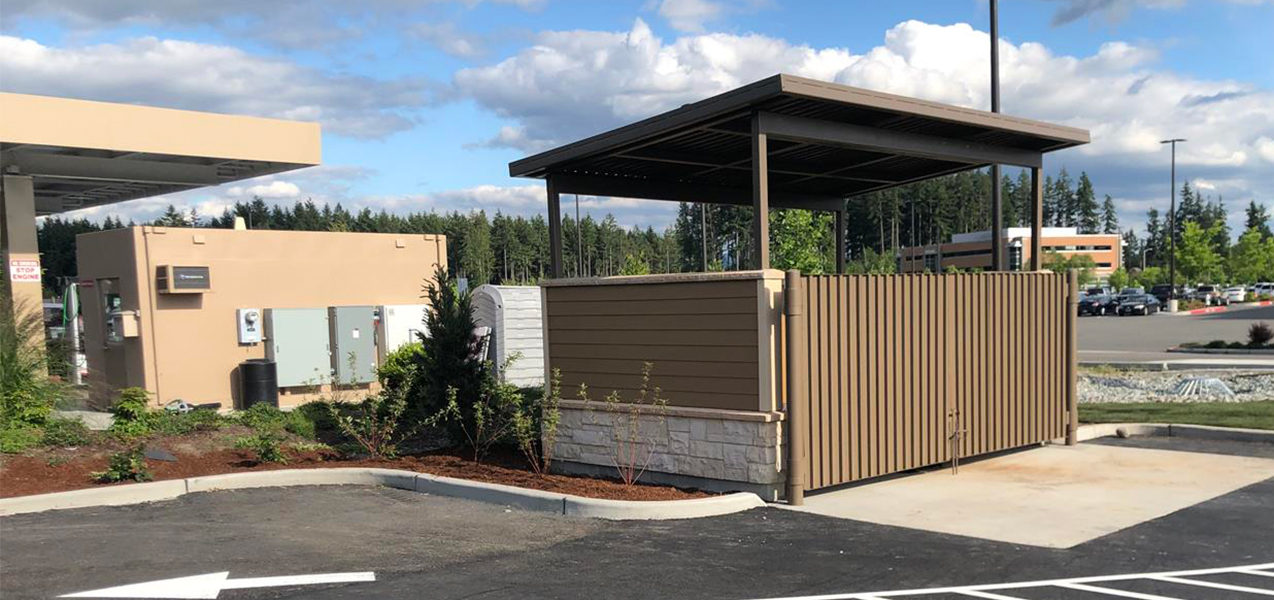 An open-air structure conceals dumpsters in the parking lot of Valvoline Instant Oil Change.