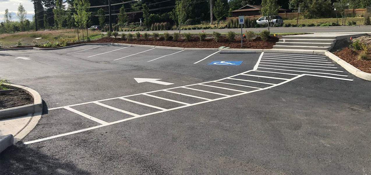 The landscaped perimeter of the parking lot and painted pedestrian crosswalks at Valvoline, a Tri-North project.