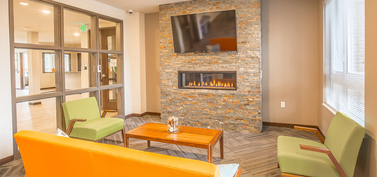 Sitting area with chairs and television inside the Veritas Village apartment complex in Madison, Wisconsin.
