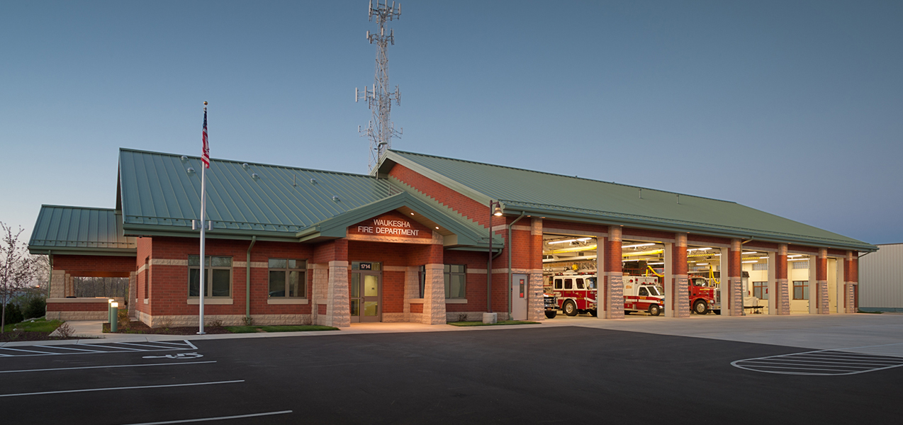 Front entrance, garage doors, of Waukesha Fire Department at night showcasing work by Tri-North Builders.