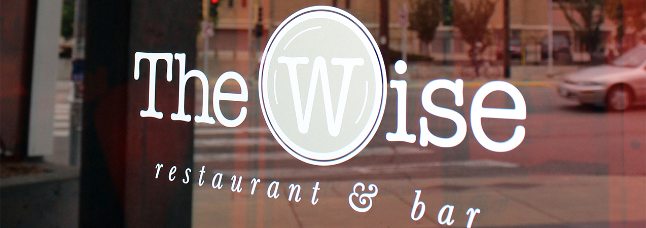 Close up of The Wise at Hotel Red restaurant logo on window in Madison, WI, a Tri-North Builders project.
