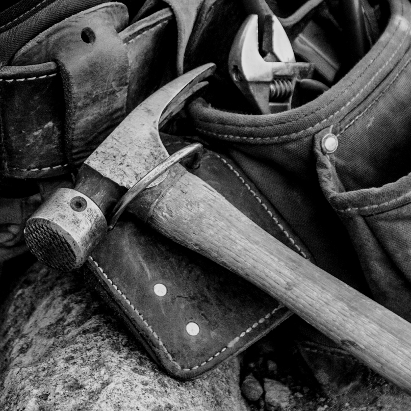 A hammer rests on a leather tool belt.